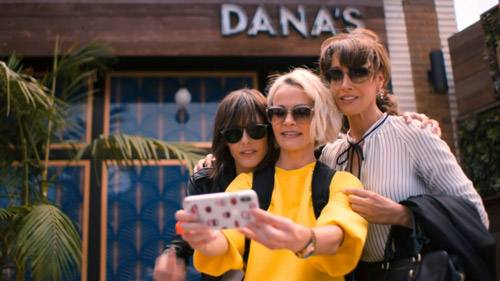 Shane, Alice, and Bette pose for a selfie outside Shane's new bar that she named