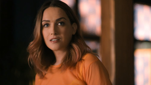 Tess is wearing an orange shirt and looks across the bar at Shane and Lena.