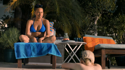 Sophie wears a blue bikini and sits on a lounge chair while talking to Finley who is in the pool.