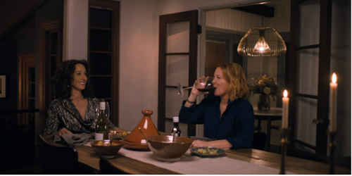 Tina drinks wine as Bette smiles at her across the dinner table.