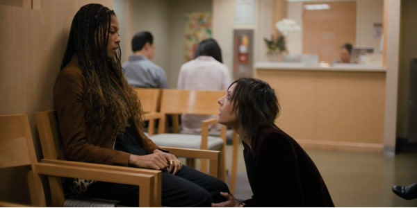 Quiars sits in a chair in the waiting room of a hospital while Shane kneels in front of her.